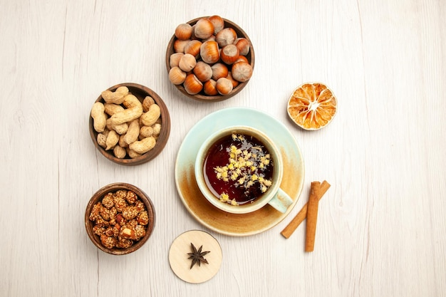 Top view different nuts inside little pots with cup of tea on white desk nut snack walnut hazelnut