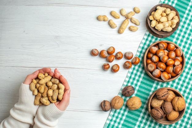 흰색 탁자에 있는 다른 견과류 땅콩 헤이즐넛과 호두를 손에 들고 탑 뷰