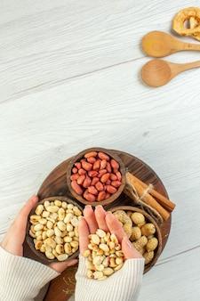 上面図白いテーブルの上のさまざまなナッツピーナッツヘーゼルナッツとクルミ