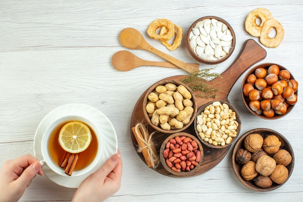 上面図さまざまなナッツピーナッツヘーゼルナッツとクルミと白いテーブルの上のお茶