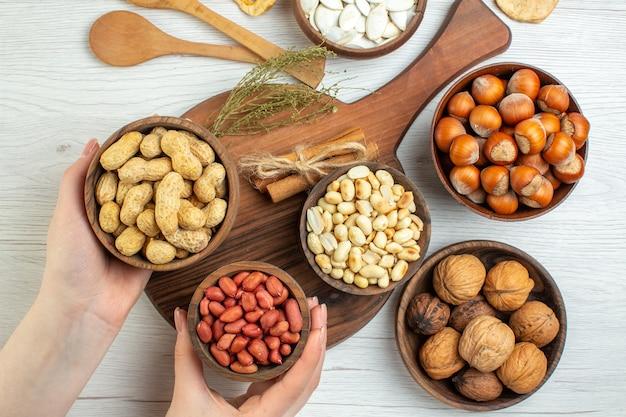 Vista dall'alto diverse noci arachidi nocciole e noci sul tavolo bianco