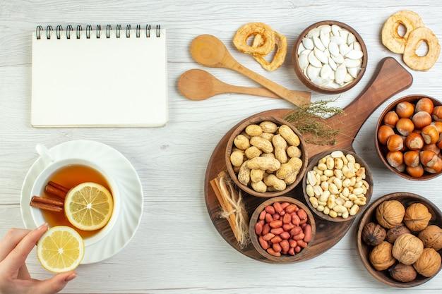 Vista dall'alto diverse noci arachidi nocciole e noci con una tazza di tè sul tavolo bianco
