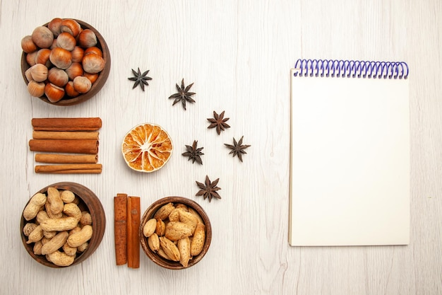 上面図白いデスクナッツスナッククルミヘーゼルナッツにシナモンとさまざまなナッツ