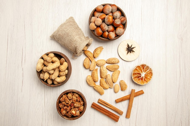 Top view different nuts with cinnamon on the white desk nut snack walnut hazelnut