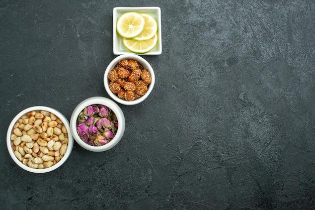 Vista dall'alto diverse noci con limone e caramelle su uno spuntino di noci con superficie scura dolce