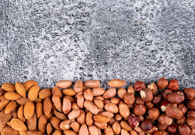 Top view different nuts with pecan, pistachios, almond, peanut, cashew, pine nuts on dark stone table