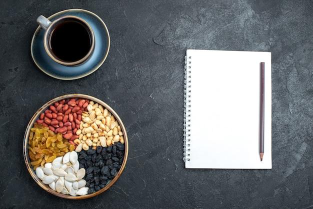 ダークグレーの背景にレーズンとコーヒーのカップとさまざまなナッツの上面図ナッツスナッククルミピーナッツ