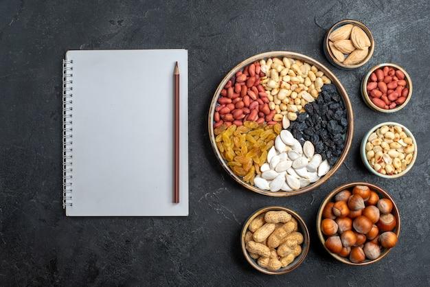 灰色の背景にレーズンとドライフルーツを含むさまざまなナッツの上面図ナッツスナックレーズンドライフルーツナッツ