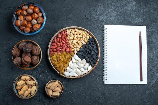 ダークグレーの背景にレーズンとドライフルーツを添えたさまざまなナッツの上面図ナッツスナックヘーゼルナッツクルミピーナッツ