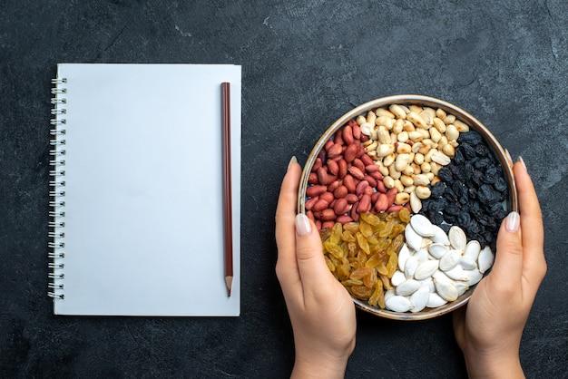 グレーのデスクナッツスナックヘーゼルナッツクルミピーナッツにレーズンとドライフルーツを添えたさまざまなナッツの上面図