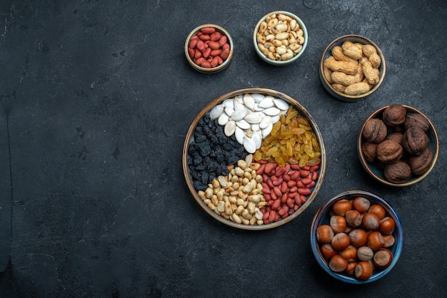 Top view different nuts with raisins and dried fruits on dark-grey background nut snack hazelnut walnut peanut