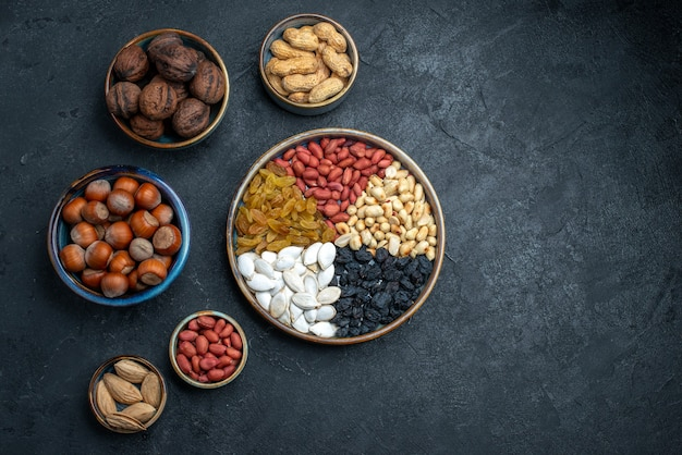 Top view different nuts with raisins and dried fruits on dark grey background nut snack hazelnut walnut peanuts