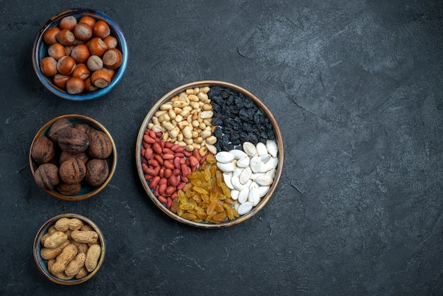 Top view different nuts with raisins and dried fruits on dark-grey background nuts snack hazelnut walnut peanuts