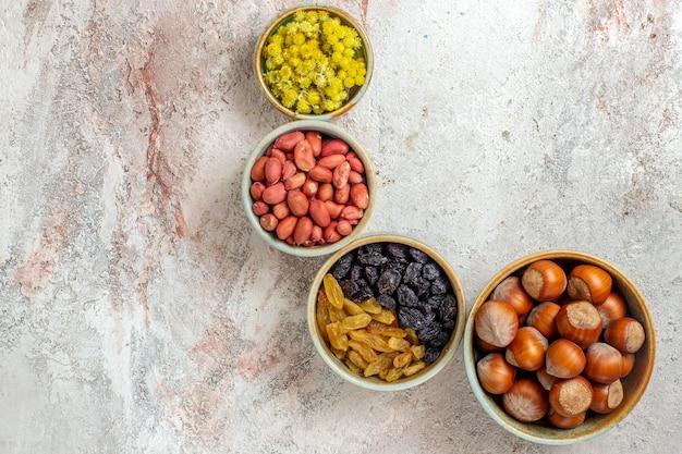 Vista dall'alto diverse noci con uvetta su sfondo bianco spuntino con noci uvetta