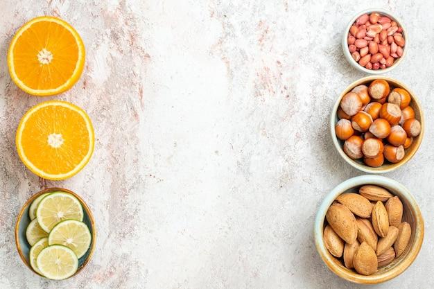 上面図白い背景にスライスしたオレンジとさまざまなナッツフルーツ柑橘類ナッツスナック