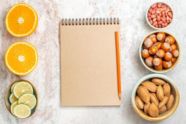 흰색 배경에 슬라이스 오렌지와 상위 뷰 다른 견과류 과일 감귤 너트 스낵
