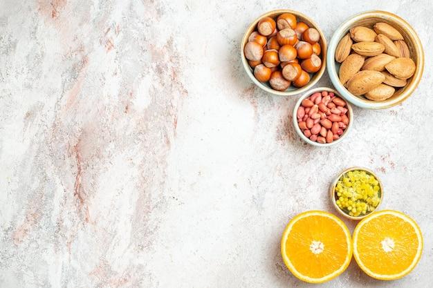Vista dall'alto diverse noci con arancia affettata su sfondo bianco frutta agrumi spuntino Foto Gratuite