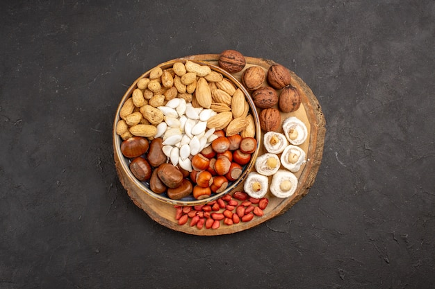 Top view of different nuts with white confitures on dark surface