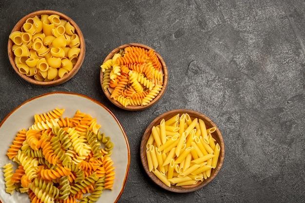 Vista dall'alto del prodotto crudo di diversa composizione di pasta all'interno di piatti su pasta grigia per cottura cruda di pasta