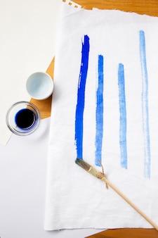 Вид сверху разные плоские кисти и синие линии