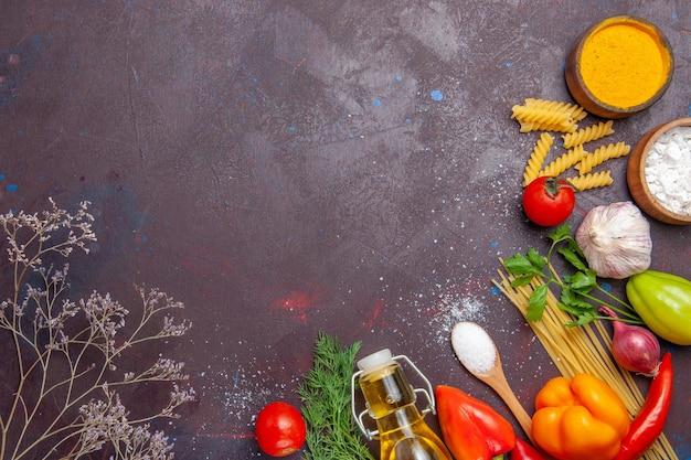 Vista dall'alto diversi prodotti pasta cruda diversi condimenti e verdure su sfondo scuro dieta salute cibo crudo