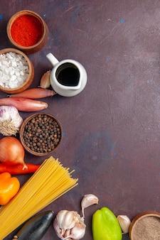 暗い背景の食事食品野菜健康サラダに野菜と調味料を含むさまざまな製品の上面図