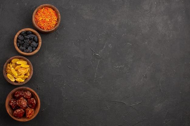 Top view different raisins inside little pots on dark space