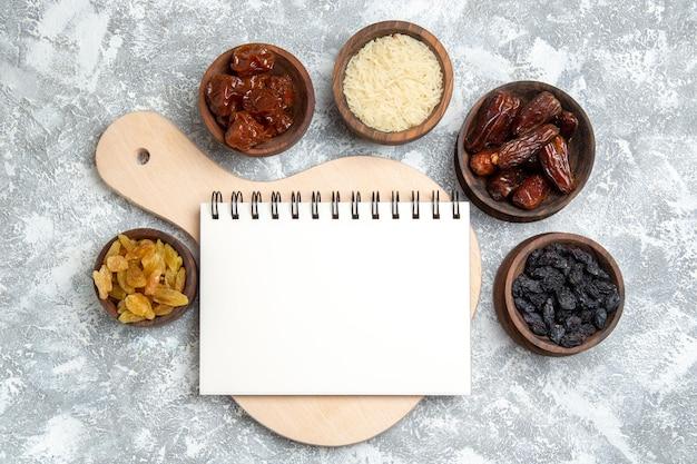 空白のメモ帳と小さな鉢の中のさまざまなレーズンの上面図