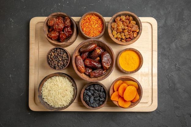 Вид сверху разные изюм хурма и другие сухие фрукты на серой поверхности сухой фруктовой муки кислой
