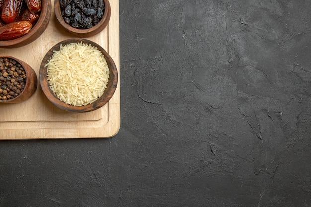 Vista dall'alto diverse uvette khurma e altri frutti secchi sulla superficie grigia farina di frutta secca acida