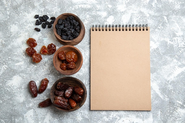 Top view different raisins with notepad on white space