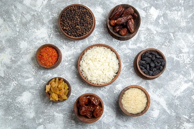 Top view different raisins with seasonings and rice on white space
