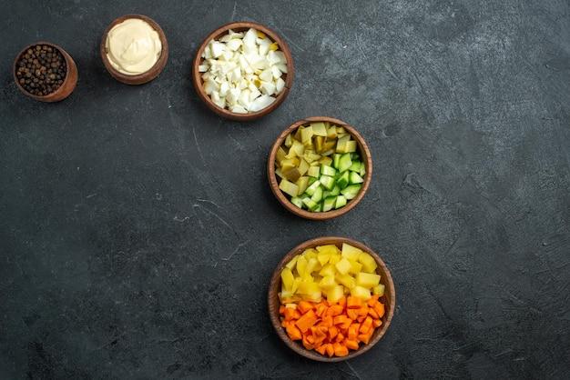 Vista dall'alto diversi ingredienti di insalata sulla superficie grigia spuntino di verdure di insalata di insalata