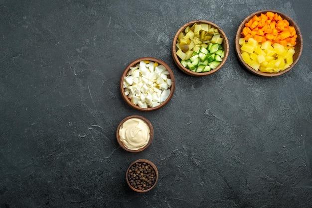上面図さまざまなサラダ材料スライスした野菜の暗い表面サラダ健康食事スナックランチ食品