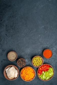 Vista dall'alto diversi ingredienti per insalata con pollo su dieta salutare per insalata da tavola scura