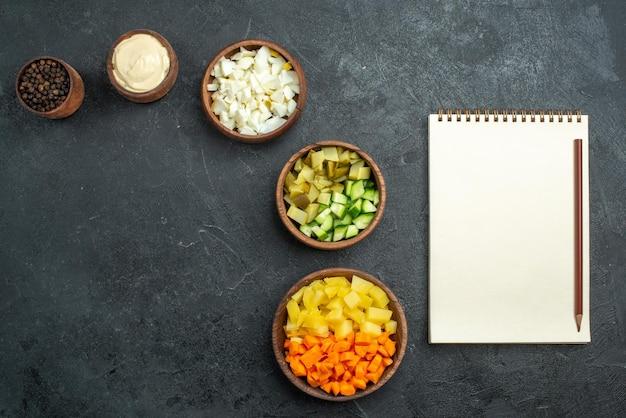 灰色の表面にメモ帳が付いたさまざまなサラダ材料の上面図サラダ野菜ミールスナック