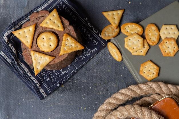 Вид сверху на разные соленые крекеры, выложенные на сером фоне, хрустящие закуски, фото