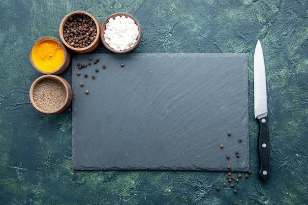 Top view different seasonings on dark blue surface food salt pepper photo color