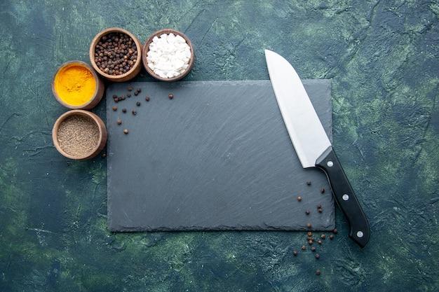 Vista dall'alto diversi condimenti sulla superficie blu scuro cibo spezie sale pepe foto colori