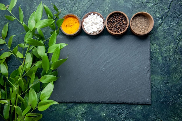 Top view different seasonings on dark blue surface photo food spice salt pepper
