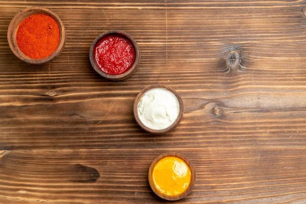 Vista dall'alto di diversi condimenti all'interno di piccoli vasi su un tavolo di legno marrone