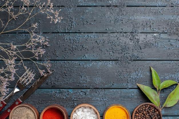 Vista dall'alto diversi condimenti all'interno di piccoli vasi su una scrivania blu scuro spigolosa pepe piccante