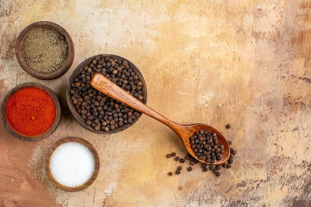 木製の机の上の小さな鉢の中のさまざまな調味料の上面図