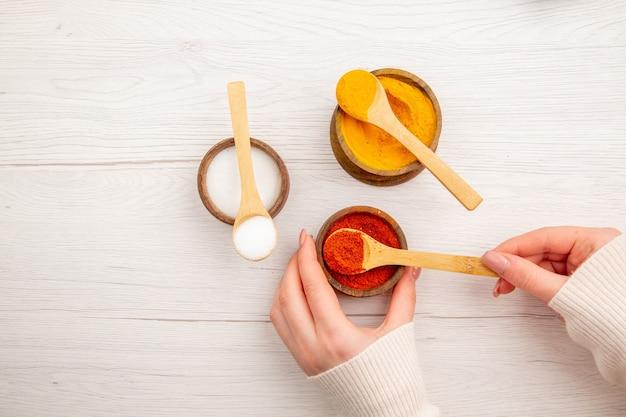 Vista dall'alto diversi condimenti all'interno di piccoli vasi su una scrivania bianca color pepe cibo piccante foto calda
