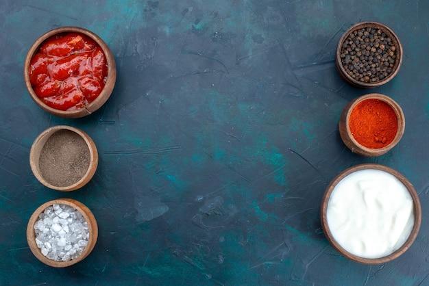Вид сверху разные приправы на темно-синем пищевом ингредиенте столовой еды