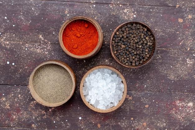 Vista dall'alto di diversi condimenti sale pepe all'interno di ciotole marroni su marrone, ingrediente di sale pepe essiccato
