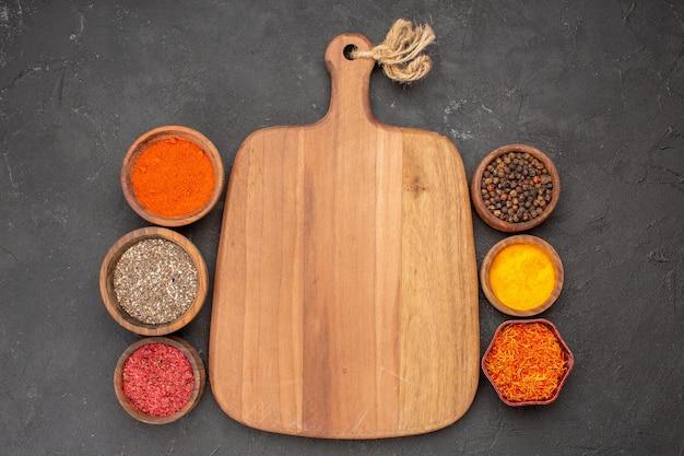 Vista dall'alto di condimenti diversi ingredienti piccanti all'interno di piccoli vasi sul nero