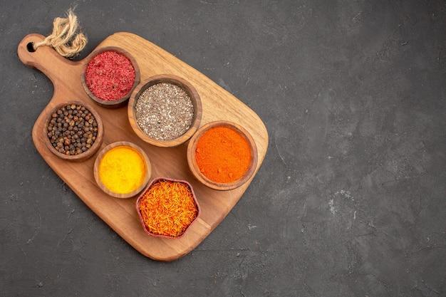Vista dall'alto di condimenti diversi ingredienti piccanti all'interno di pentole su nero