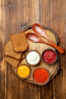 Top view of different seasonings with black bread loafs on brown wooden table
