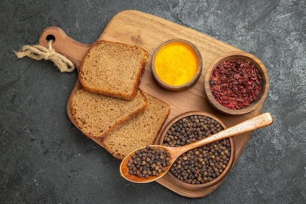 Вид сверху разные приправы с буханками хлеба на сером столе, пряный горячий хлеб